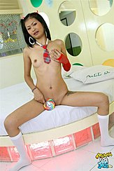 Nina Sitting On Edge Of Bed Nude Hand Over Her Small Breast Holding Lollipop Over Her Pussy In Socks