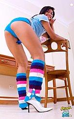 Bending Over Chair Looking Over Her Shoulder Wearing Blue Shorts In High Heels
