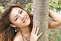 Kathy Ramos strips between trees and bares small tits