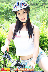 Riding Bike Long Hair Under Her Helmet Wearing Denim Shorts