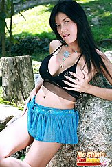 Mo Chada Leaning Against Rock Hand On Breast In Short Skirt Long Hair