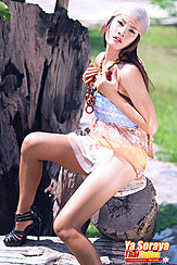 Seated On Tree Stump Wearing Bandana In High Heels