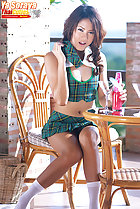 Seated at table wearing green plaid skirt in socks