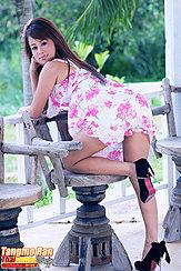 Tangmo Ran Bending Over Chair Looking Over Her Shoulder In Dress Wearing High Heels