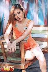 Sitting On Bench Wearing Orange Dress Long Hair