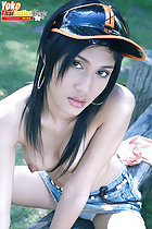 Seated topless tendrils of long hair falling over her small breasts wearing sun visor