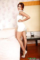 Anny standing beside bed wearing white dress hand on hip in high heels